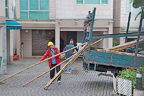屋宇署視察後,有貨車運載搭棚用的竹枝,由工人搬進4號屋。(蔡雯文/大紀元)