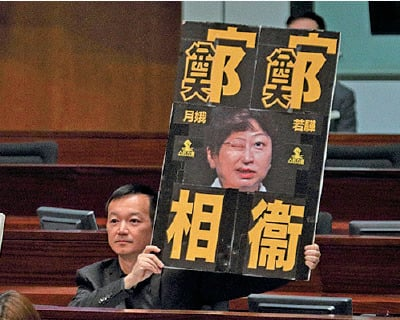 人民力量議員陳志全手持「鄭鄭相衛」的示威牌。(李逸/大紀元)