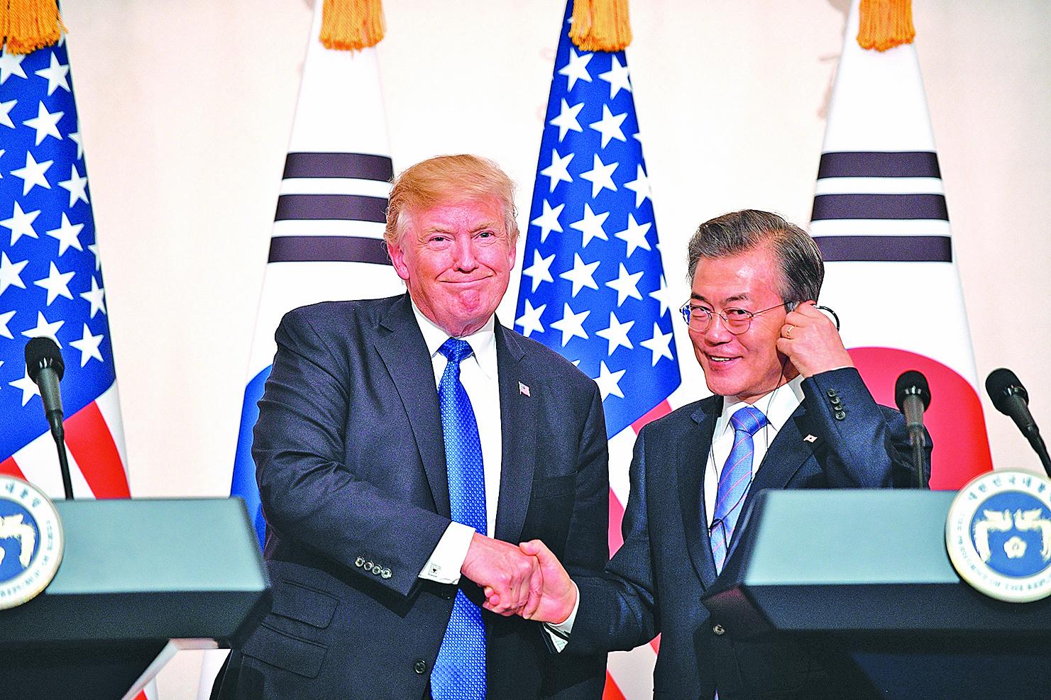 北韓新年對南韓拋「橄欖枝」,考驗美韓關係。不過特朗普(左)和南韓總統文在寅(右)表示,無論北韓耍甚麼招數,兩國都會協力應對。(AFP)