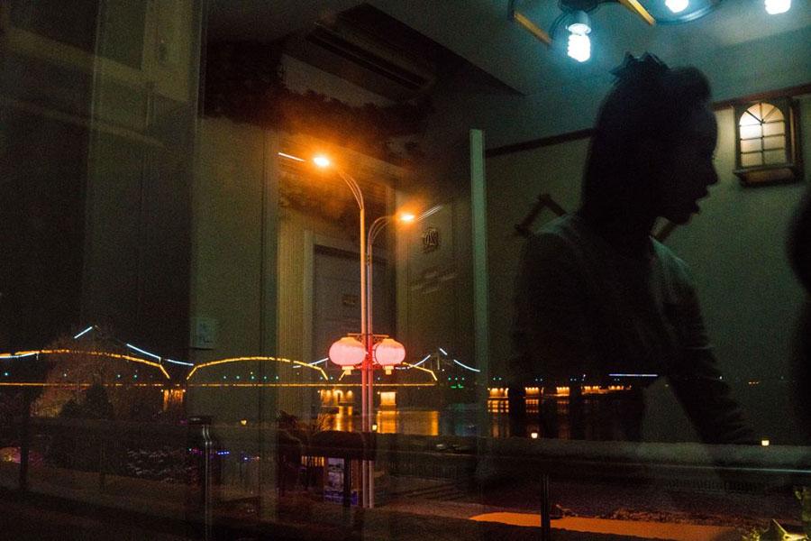 圖為1月8日,丹東一家北韓餐廳的服務員的影子映在玻璃上。(CHANDAN KHANNA/AFP/Getty Images)