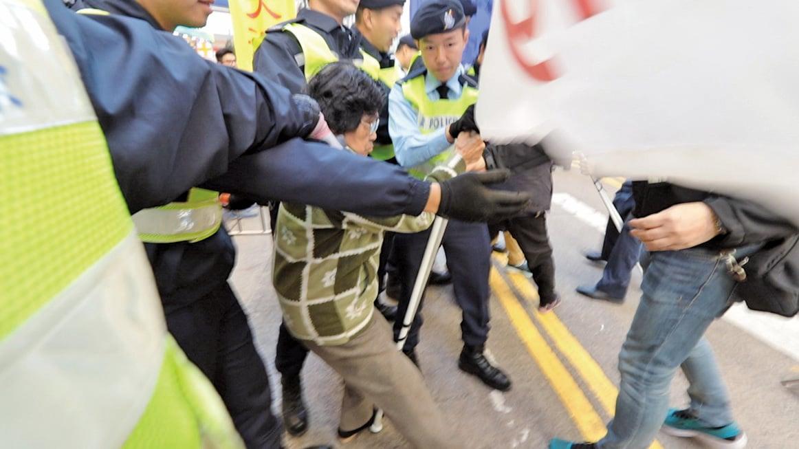 五、六名警員包圍一名80多歲的法輪功學員,前後拉扯她手中的橫幅,令她跌倒在地,一度在地上拖行。(大紀元)