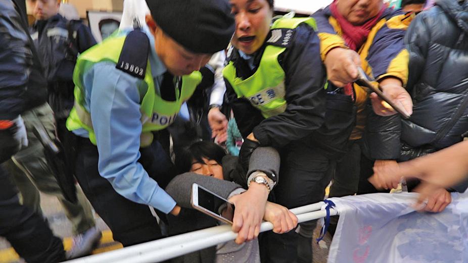 一名女法輪功學員遭多名警員拖倒在地,繼續緊抓正被強奪的橫幅。(大紀元)
