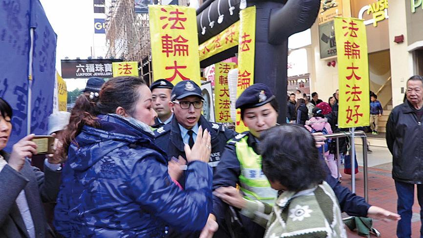 青關會頭目之一肖小蓉(左邊藍衣者)向警方出言施壓,其後警方對法輪功採取行動。(大紀元)