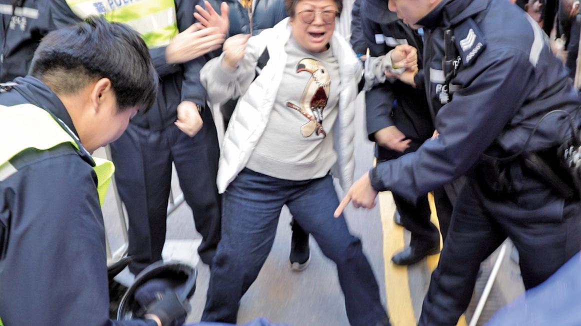 法輪功學員李小姐遭多名警員拉扯。她周六當天在警方推撞期間倒地,不適送院。