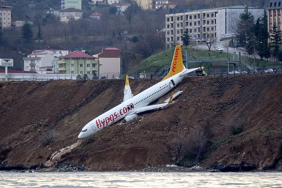 周六(1月13日),一架客機在土耳其北部一個沿海機場滑出跑道,從距離黑海幾英尺遠的懸崖邊滑落,倒栽蔥掛在懸崖邊。(AFP PHOTO / DOGAN NEWS AGENCY)