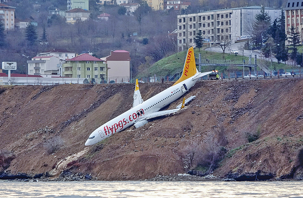 上周六(1月13日),一架客機在土耳其北部一座沿海機場滑出跑道,倒栽蔥掛在懸崖邊。(AFP)