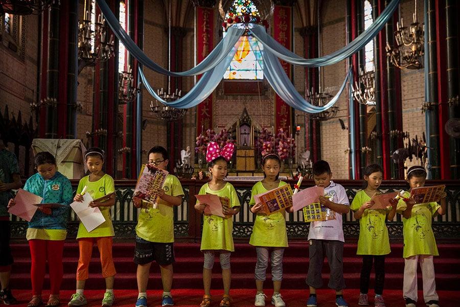 中共新修訂的《宗教事務條例》下月施行,據「自由之家」16日發佈的報告指出,新規定進一步限縮宗教自由的範圍,特別是對於兒童的「宗教教育」。圖為北京小朋友們2014年參加天主教夏令營。(Kevin Frayer/Getty Images)