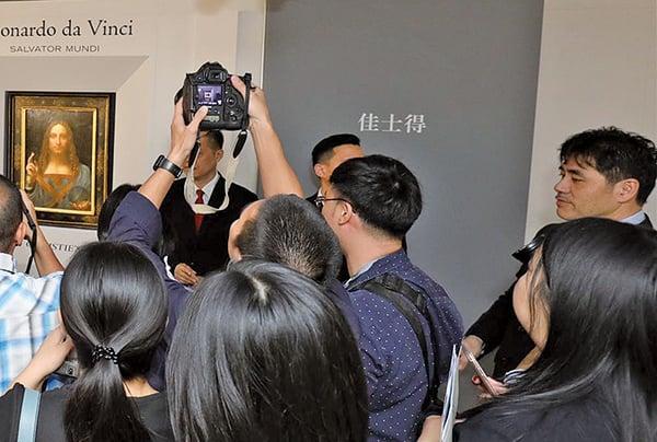 佳士得10月發佈的達文西名畫《救世主》在香港拍賣前傳媒預覽當日相片,李振成(最右方男子)當日在場維持秩序。(佳士得圖片)