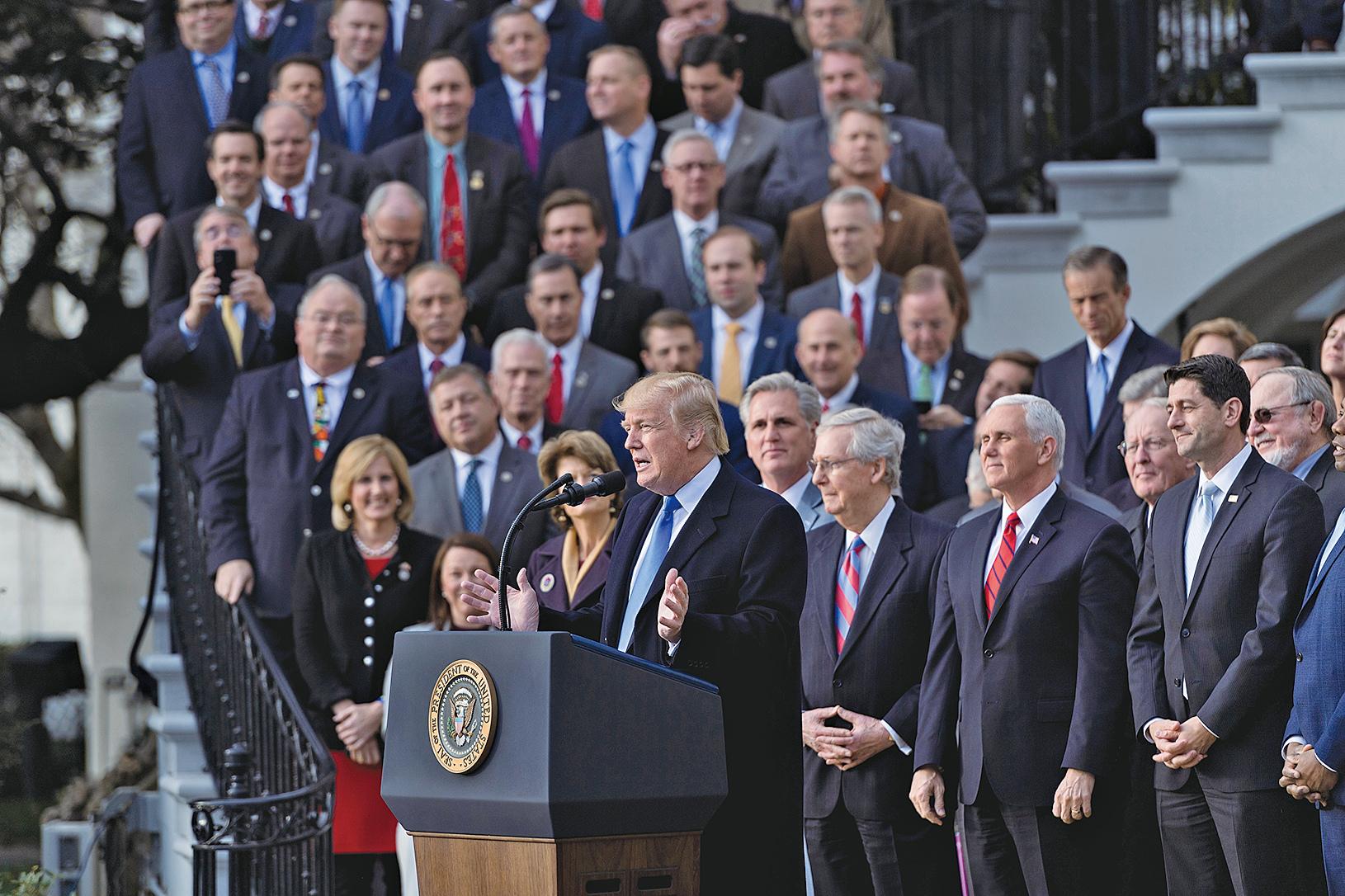 2017年12月20日,特朗普在白宮和副總統彭斯及共和黨國會議員慶祝減稅法案過關。(AFP)