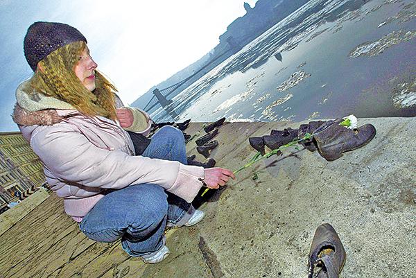 匈牙利女孩在布達佩斯多瑙河畔獻花,悼念二戰期間被推進多瑙河的匈牙利猶太人。(Getty Images)