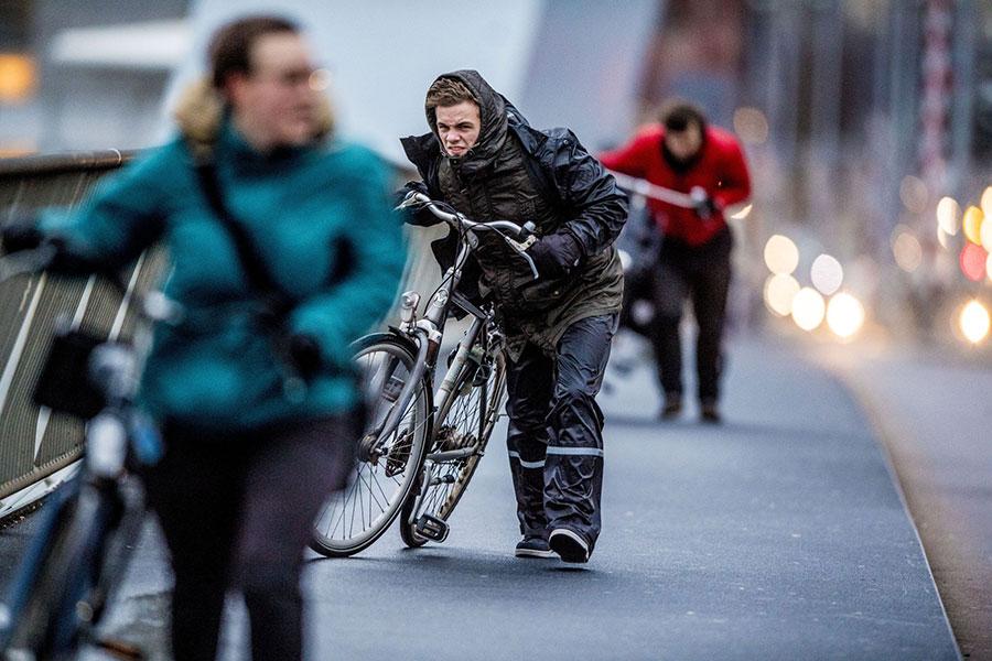 1月18日,強風襲擊荷蘭,鹿特丹民眾逆風牽單車行走。(Robin UTRECHT/ANP/AFP)