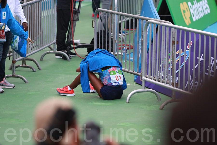 埃塞俄比亞冠軍跑手杜利莎(Gulume Tollesa Chala)在衝線後一度感到身體不適嘔吐,坐在地上復原。(陳仲明/大紀元)