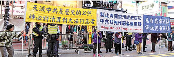 法輪功學員在青關會道具前和平展示「制止青關會污辱法輪功」、「停止迫害」等橫幅。(大紀元)