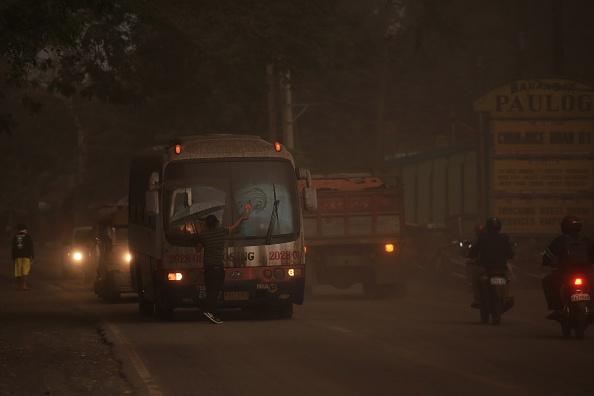 馬榮火山22日噴發,大量煙塵和火山灰讓附近地區陷入一片黑暗,駕駛者要開燈並使用擋風玻璃刮水器才能看清路面。(CHARISM SAYAT/AFP/Getty Images)