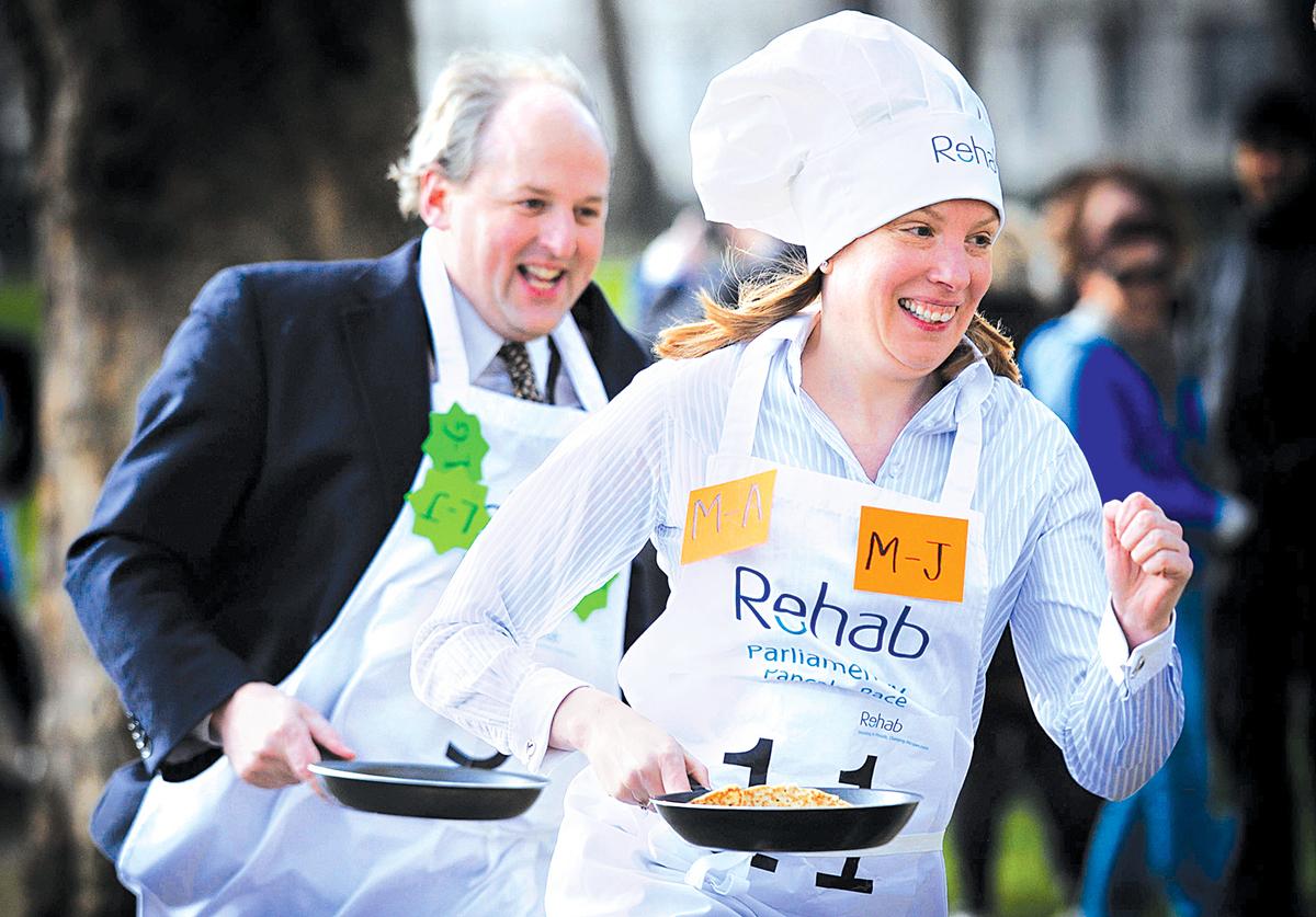 英國新任的「孤獨大臣」孔芮忻(前)2012年參加英國國會的端煎餅賽跑慈善活動。(大紀元資料室)