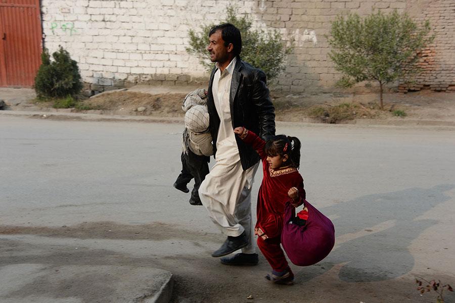 賈拉拉巴德(Jalalabad)的一座拯救兒童救援機構的大樓周三遭遇自殺式爆炸襲擊,至少2人死亡,20人受傷。圖為一男子領著兩個孩子逃走。(NOORULLAH SHIRZADA/AFP/Getty Images)
