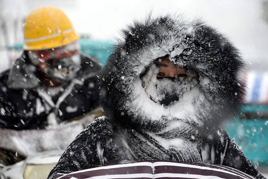 2018年1月25日,中國皖東亳州市降雪,圖為一名騎著摩托車的女子。(AFP/Getty Images)