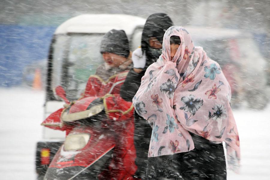 2018年1月25日,中國皖東亳州市降雪,人們在雪中行走。(AFP/Getty Images)