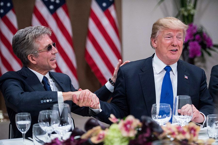 特朗普周四(1月25日)晚間設宴款待歐盟跨國公司的企業家們,與會的歐盟工商界領袖稱讚特朗普推行的減稅改革。圖為SAP公司行政總裁孟鼎銘(Bill McDermott)與特朗普在晚宴期間握手。(NICHOLAS KAMM/AFP/Getty Images)