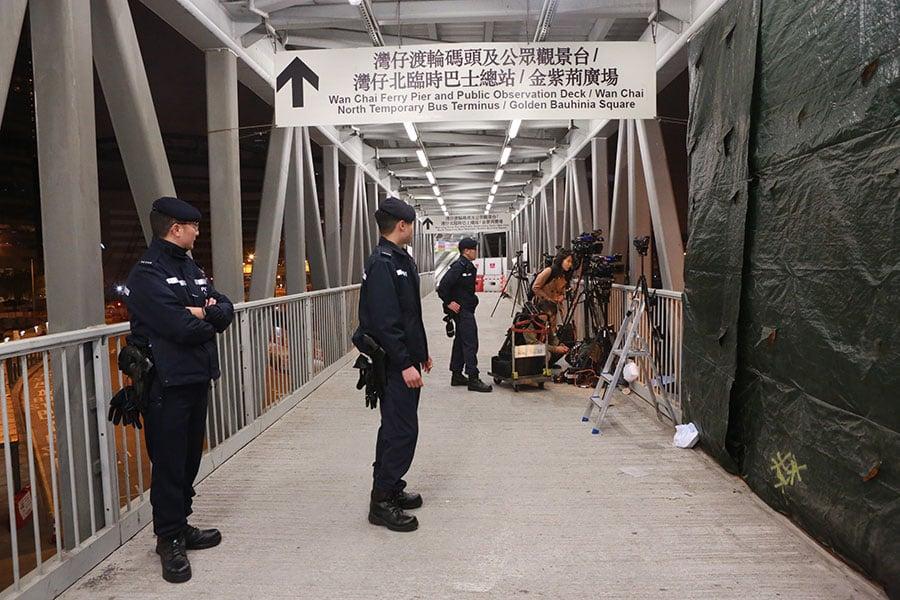 晚上11時,警方採取全面封鎖行動,在海港中心行人天橋上的傳媒記者需要撤離。(陳仲明/大紀元)