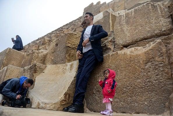 受到埃及官方邀请,世界最高男性科森(圖左)與最矮女性阿姆奇(圖右)在吉薩金字塔前拍攝照片,以推廣埃及旅遊。(STRINGER/AFP/Getty Images)