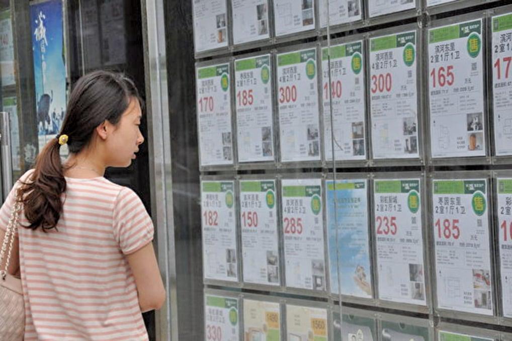北京樓市在去年量價齊跌。圖為北京的一位市民正在查看房地產公司貼出的信息。(大紀元資料室)