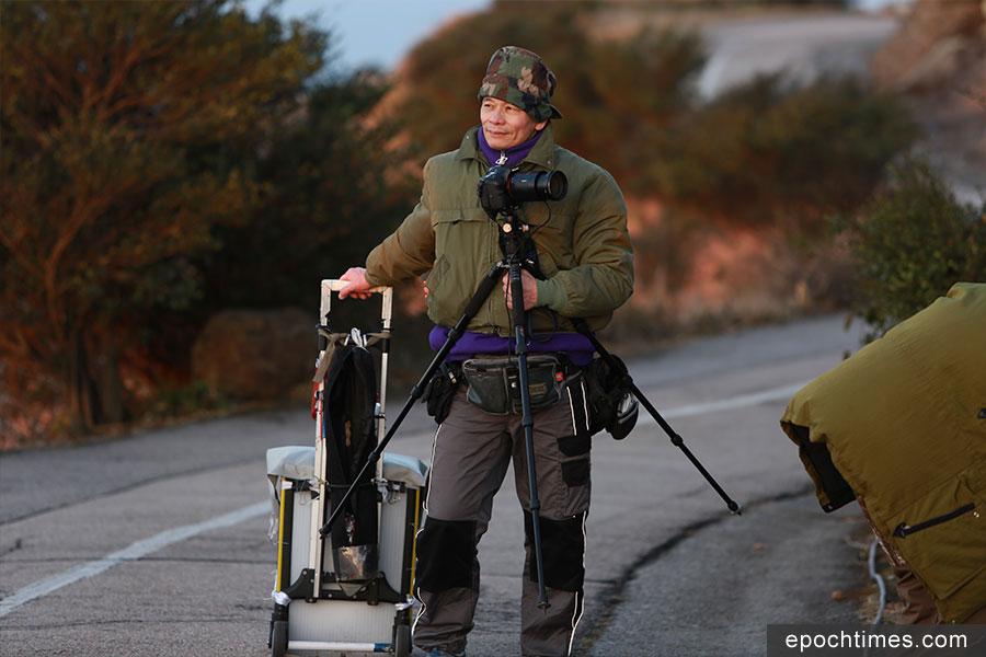 經常到訪大帽山的建築業退休人士阿明拖著手推車,昨午已到山頂看日落,並留在山上等候今晨的日出。(陳仲明/大紀元)