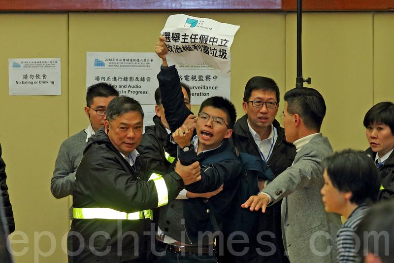 黃之鋒等香港眾志成員趁候選人簡介會進入會場抗議。(李逸/大紀元)