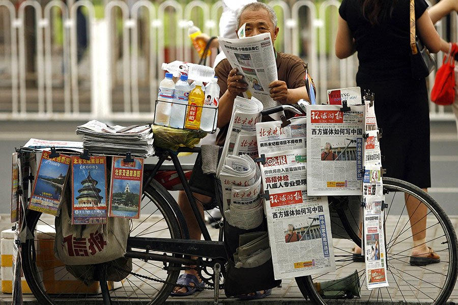 在中共的精心操弄下,當今中國的媒體,早已不知該肩負的責任。圖為零售商在北京街頭賣報一景。(PETER PARKS/AFP/Getty Images)