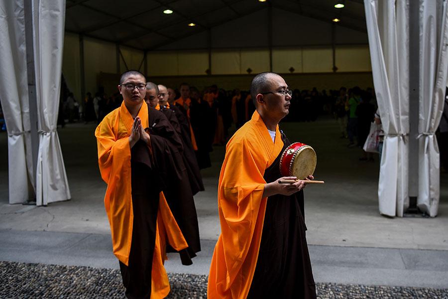 圖為2017年9月5日,135歲的上海玉佛寺大殿正式搬遷期間,佛教僧侶在寺內祈禱。(CHANDAN KHANNA/AFP/Getty Images)
