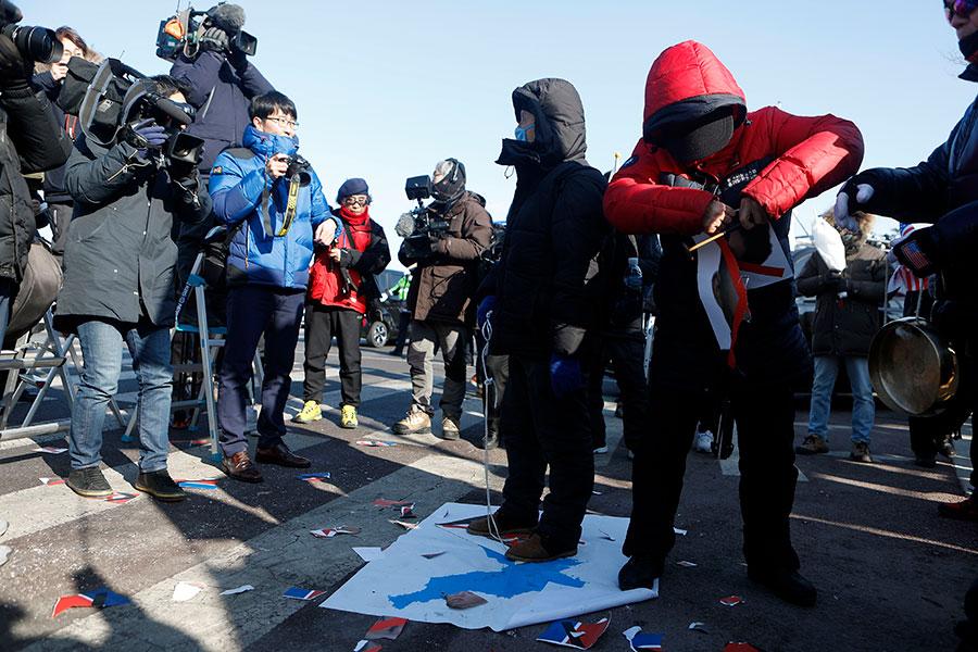 南北韓女子冰球隊周日(4日)首度為平昌冬季奧運舉行熱身賽,結果以1比3敗給瑞典隊,球場外南韓示威民眾踩踏統一旗以示抗議。(Woohae Cho/Getty Images)