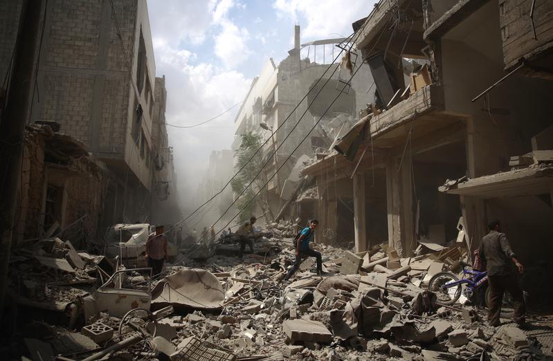 2016年2月11日,敘利亞內戰五年,令全國一半以上的人流離失所,至今已有47萬人在內戰中死亡。圖為去年8月31日,大馬士革東部的反抗軍據點杜馬區(Douma),敘軍轟炸後,居民走在炸毀的街道上。(ABD DOUMANY/AFP/Getty Images)