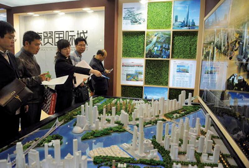 4月,滬深樓市均出現量價齊跌的現象。圖為在房地產交易會上,主辦方在向買主介紹新房。(圖/Franko Lee/AFP/Getty Images)