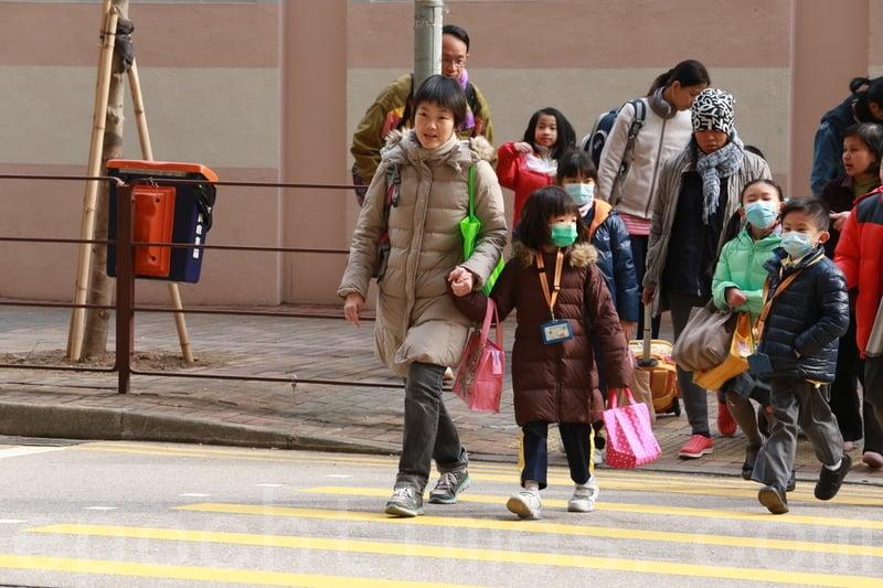 本港爆發流感,教育局宣佈幼稚園及小學提前明日起放黃曆新年假期。圖為今日下午家長接子女放學情況。(陳仲明/大紀元)