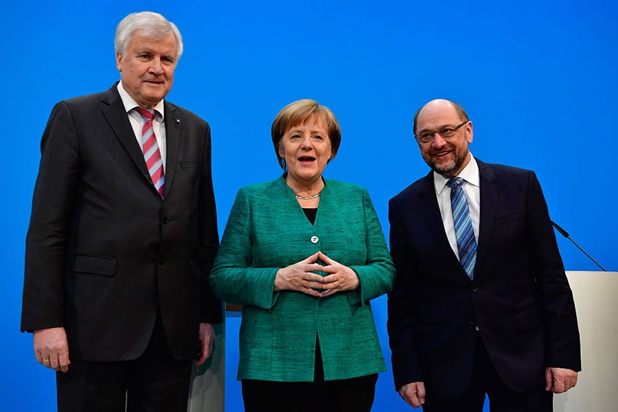 德國大聯合政府組閣協議終於談妥,4個多月的政治僵局有望終結。圖為默克爾(中)與兩位合作夥伴召開新聞發佈會。(TOBIAS SCHWARZ/AFP/Getty Images)
