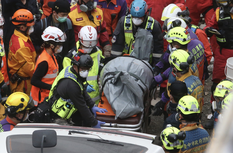 台灣花蓮強震造成花蓮市雲門翠堤大樓嚴重傾斜,2月9日下午搜救現場再發現加拿大籍香港夫婦二人遺體,搜救人員合力將遺體送上救護車。(中央社)