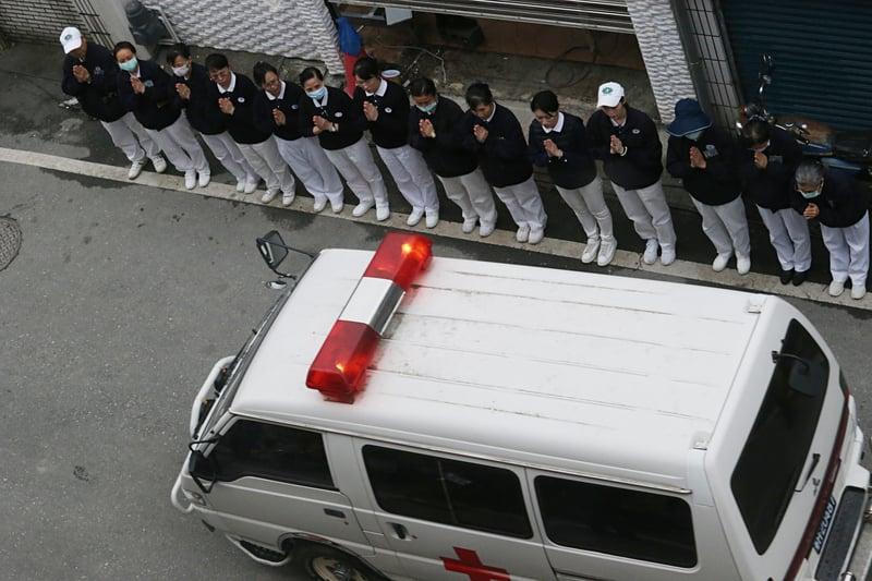 台灣花蓮強震釀災,花蓮市雲門翠堤大樓搜救現場2月9日下午再發現加拿大籍香港夫婦兩人遺體,隨後以救護車載離,路旁民眾雙手合十向罹難者致哀。(中央社)