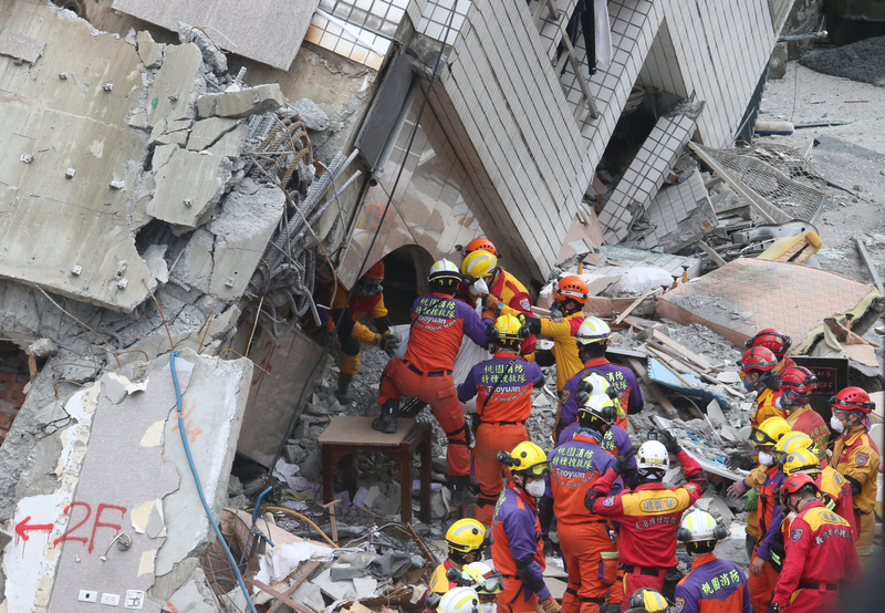台灣花蓮強震,雲門翠堤大樓搜救現場2月9日發現加拿大籍香港夫妻,但已無生命跡象,確定罹難,下午3時許搜救人員合力先將其中一人遺體送出大樓外。(中央社)