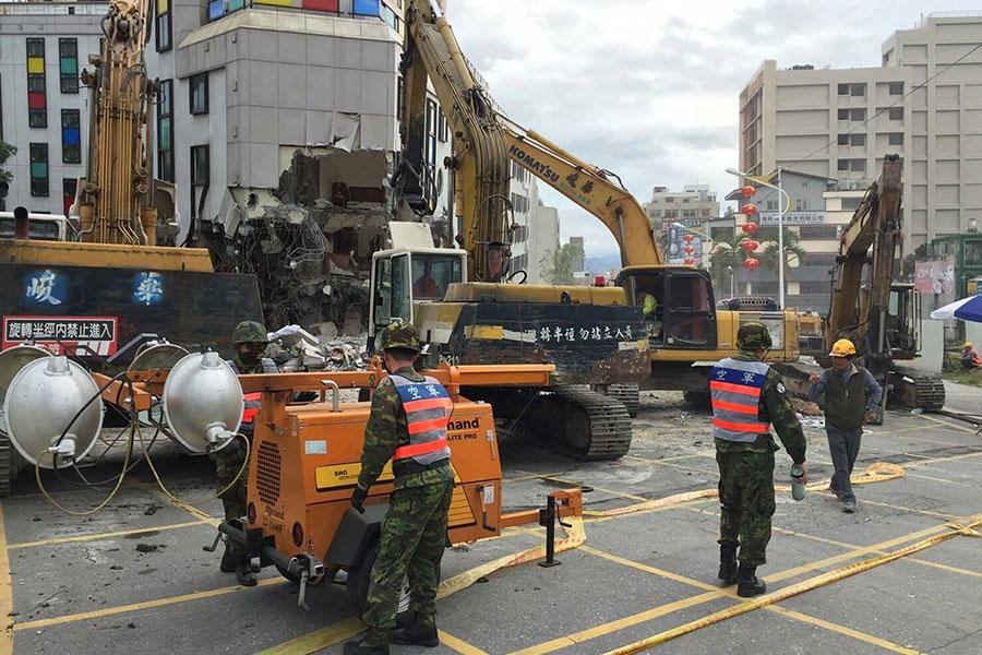 花蓮市區傾塌的統帥大飯店9日清晨已大規模開拆,空軍並支援照明燈車加速拆除速度。(中央社)