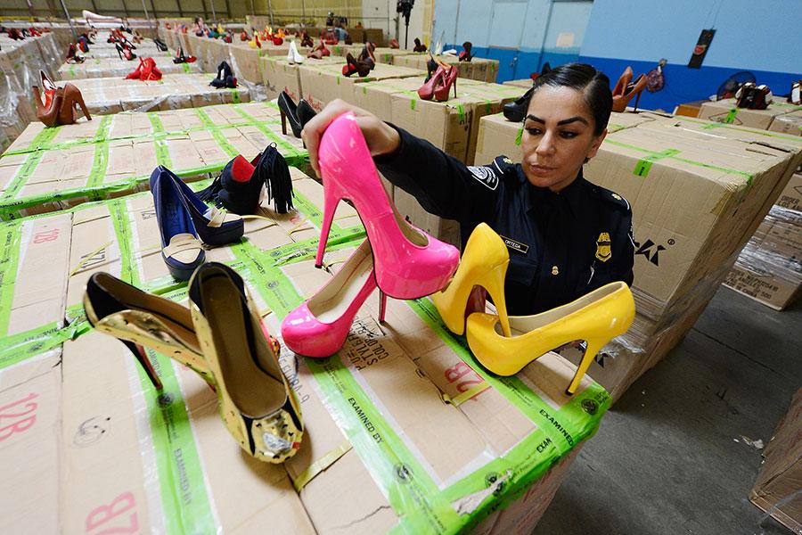 2012年8月16日,美國海關和邊境保護局官員伊麗莎白・奧爾特在加州長灘市的轉移倉庫展示假冒Louboutin高跟鞋。7月27日至8月14日期間,洛杉磯和長灘海港共檢獲了五批中國貨物,其中包含超過兩萬雙侵犯法國設計師商標的高跟鞋,潛在零售價值為1800萬美元。(Kevork Djansezian/Getty Images)