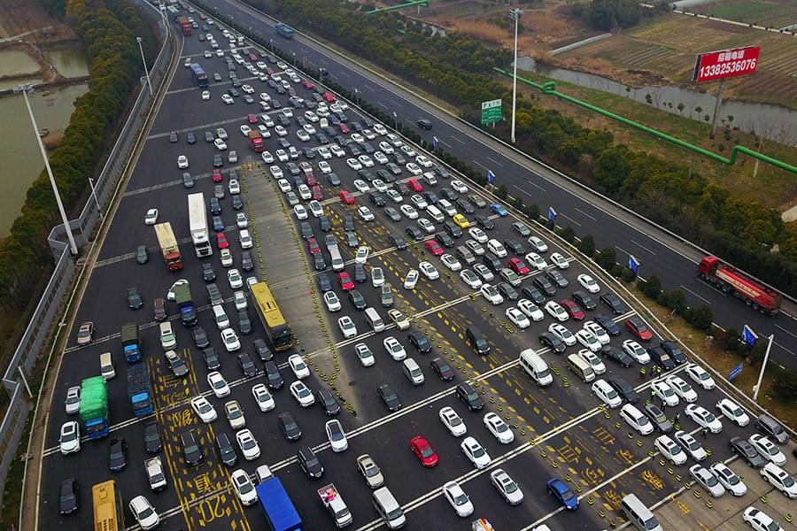 2月10日,大陸過年前最後一個周末迎來返鄉潮高峰,多個大城市高速公路擁堵,其中廣東出省高速車龍一度長達22公里。圖為10日,江蘇蘇州市等待在瀋海高速公路收費站的車輛鳥瞰圖。(VCG/Getty Images)