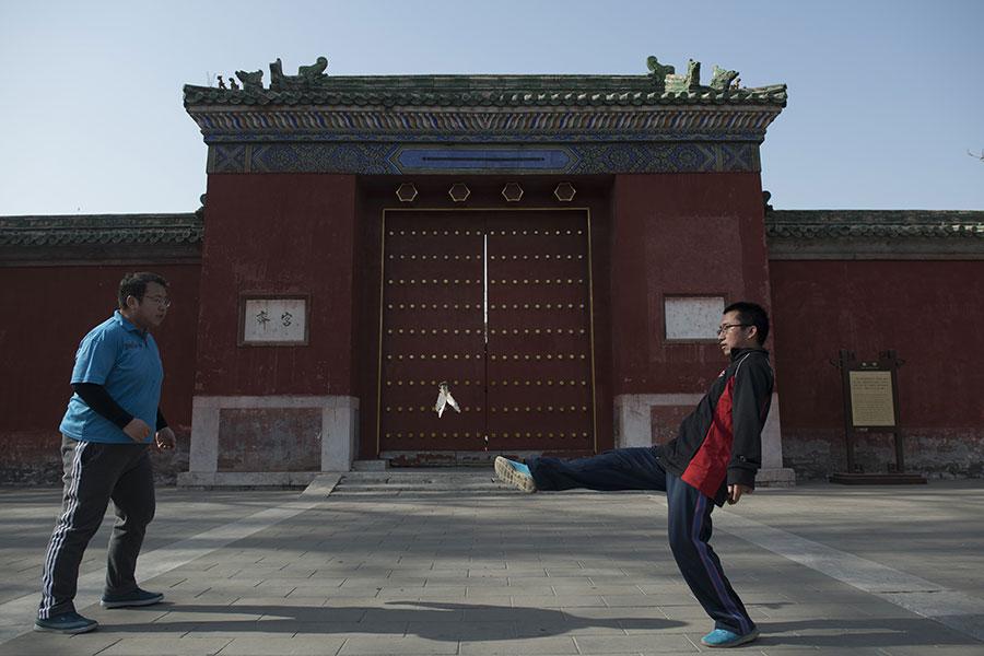 圖為2018年2月1日,兩個中國人在北京地壇公園踢毽子。(NICOLAS ASFOURI/AFP)
