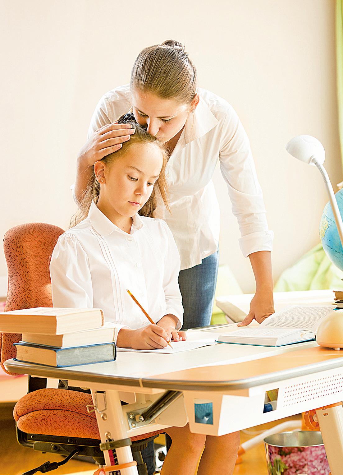 母親擁抱、讚美正在做功課的女兒。(fotolia)