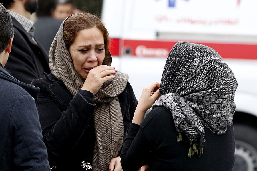 周日(2月18日),一架伊朗飛機在伊朗中部的山區墜毀。飛機上共有66人,恐全部遇難。周一,伊朗國家媒體引述伊朗官員的話說,飛機殘骸已經找到。但伊朗航空當局表示目前無法證實這一說法。圖為一名遇難人員的家屬。(ATTA KENARE/AFP/Getty Images)