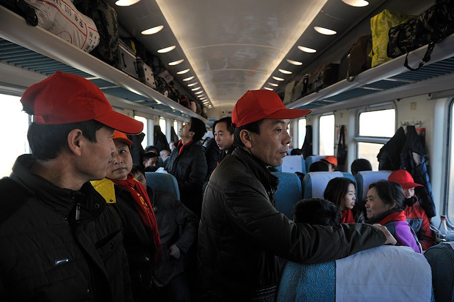 新年間,中國大陸農民工回家和家人、朋友團圓,在飯桌上大吐苦水,盼望中共專制體制早日結束。圖為今年新年前趕著回家過年的農民工們。(Tao Zhang/Getty Images)
