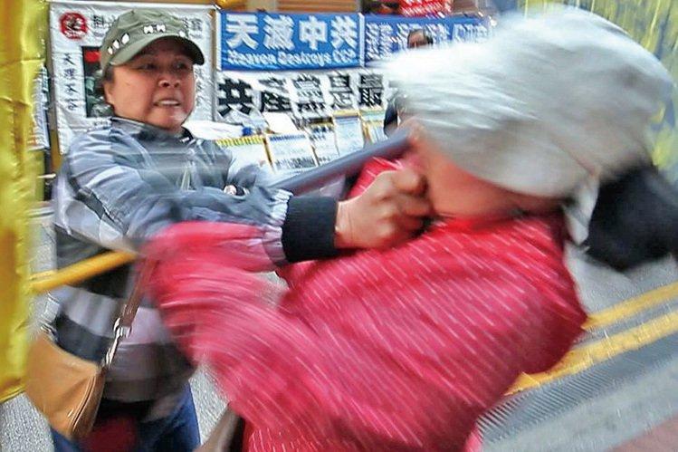 2014年3月22日,身穿便服的青關會女成員陶桂香(左)揮拳毆打法輪功學員(右),之後作勢倒地假裝昏倒。(大紀元資料圖片)