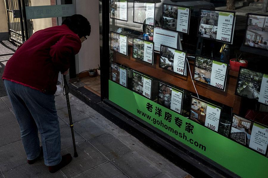 圖為2月12日,一名婦人在上海一間地產舖前觀看樓盤資訊。(JOHANNES EISELE/AFP/Getty Images)