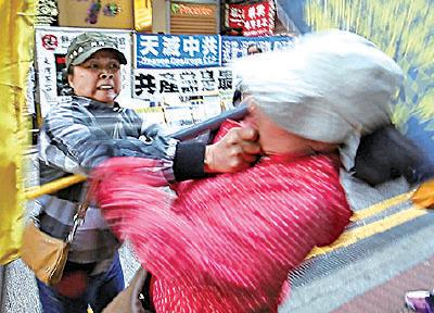 2014年3月22日,青關會女成員陶桂香在銅鑼灣毆打法輪功學員後作勢倒地,試圖誣陷法輪功學員打人。(大紀元資料圖片)