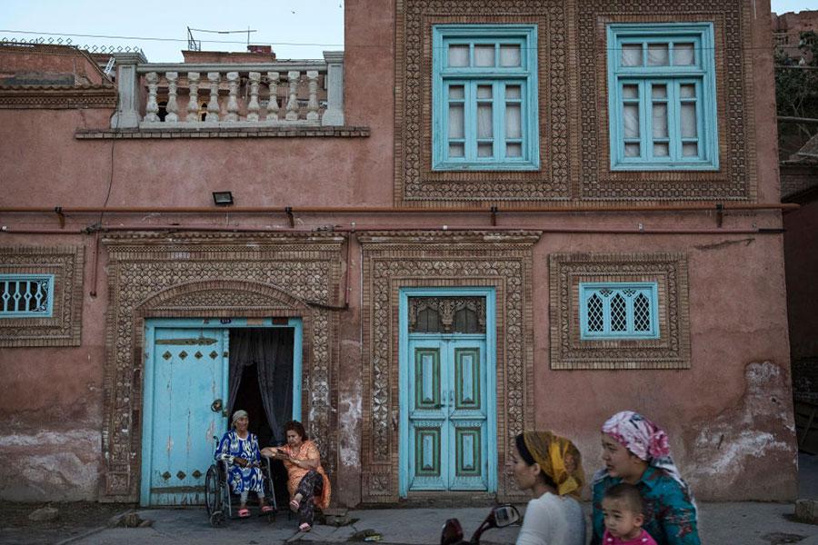 近日,多名海外維吾爾語記者在大陸的家屬被拘押。圖為6月30日新疆喀什維吾爾婦女坐在自家門外面。(Kevin Frayer/Getty Images)