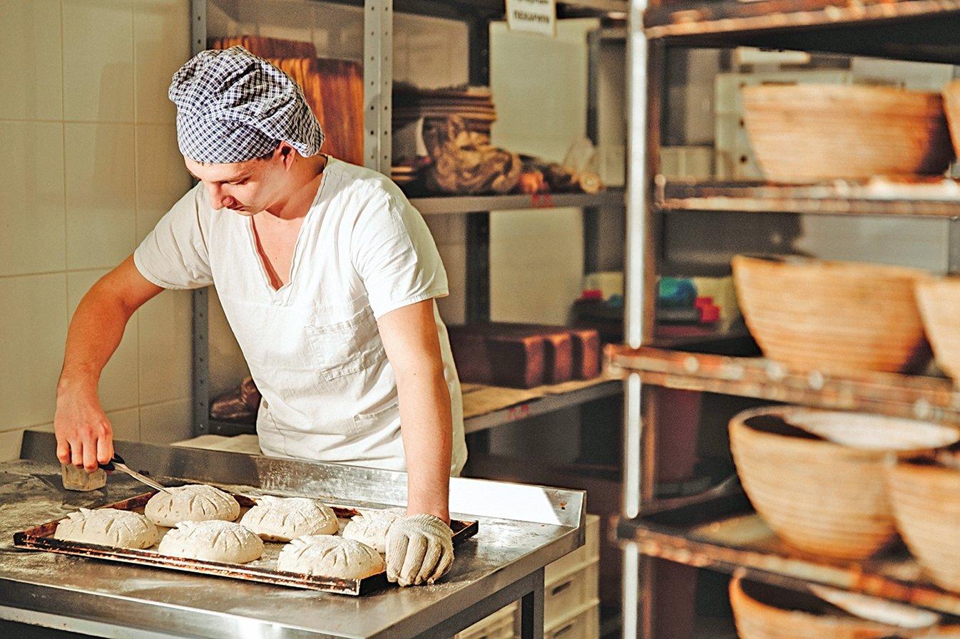 麵包師傅正在幫麵包做出割紋。